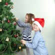 Kids decorating Christmas tree with baubles in room — Stock Photo #40581629