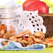 Composition with dried apples in glass jar and fresh apples in basket, on napkin, on bright background — Stock Photo