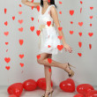 Foto de Stock  : Attractive young womwith balloons in room on Valentine Day