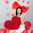 Attractive young woman with big heart and balloons in room on Valentine Day — Stock Photo #40582169