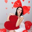 Attractive young woman with big heart and balloons in room on Valentine Day — Stock Photo