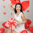 Stock Photo: Attractive young woman with gift and balloons in room on Valentine Day