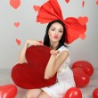 Stock Photo: Attractive young woman with big heart and balloons in room on Valentine Day