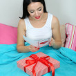 Foto de Stock  : Beautiful womwith gift in bed on Valentine Day