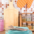Stock Photo: Plates in kitchen on table on mosaic tiles background