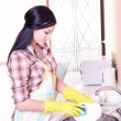 Beautiful young womwashing dishes in kitchen — Stock Photo #40583097