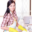 Beautiful young womwashing dishes in kitchen — Stock Photo #40583099