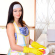 Beautiful young womwashing dishes in kitchen — Stock Photo #40583103