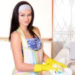Beautiful young womwashing dishes in kitchen — Stock Photo #40583107