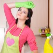 Beautiful young womcleans in kitchen — Stock Photo #40583115