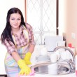 Beautiful young womcleans in kitchen — Stock Photo #40583121