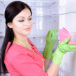 Beautiful young womwashing fridge in kitchen — Stock Photo #40583135