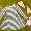 Stock Photo: Beautiful dress and gumshoes for little girl on green carpet