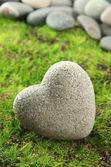 Pierre grise en forme de coeur, sur fond d'herbe — Photo