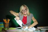 Kötü öğretmen koyu renkli arka plan üzerinde masada oturan — Stok fotoğraf