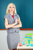 Chemistry teacher standing near table with tubes on blackboard background — Stock Photo