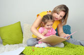 Little girl with mom read book in bed — Stock Photo
