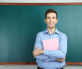 Young teacher with book near chalkboard in school classroom — Stock Photo