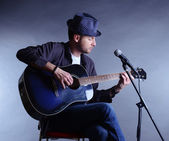 Young musician playing acoustic guitar and singing, on gray background — Stok fotoğraf