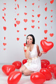 Attractive young woman with balloons in room on Valentine Day — Stock Photo