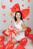 Attractive young woman with gift and balloons in room on Valentine Day — Stock Photo