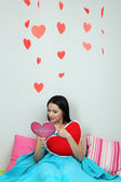 Beautiful woman reading card in bed on Valentine Day — Stock Photo