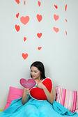Vacker kvinna läsa kortet i sängen på alla hjärtans dag — Stockfoto