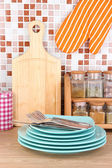 Plates in kitchen on table on mosaic tiles background — Stock Photo