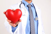 Male Doctor with red heart in his hands, isolated on white background — Stock Photo