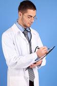 Mužské doktor s složku, na modrém pozadí — Stock fotografie