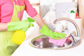 Beautiful young woman cleans in kitchen — Stock Photo