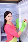 台所で美しい若い女性洗濯冷蔵庫 — ストック写真