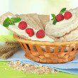 Tasty crispbread with berries in wicker basket, on green table — Stock Photo