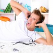 Young man relaxing on carpet and listening to music — Stock Photo #40590525