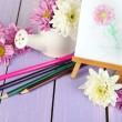 Stock Photo: Composition of flowers and small easel with picture on wooden table close-up