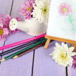 Composition of flowers and small easel with picture on wooden table close-up — Stock Photo #40590587