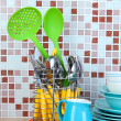 Stock Photo: Dishes and cutlery in kitchen on table on mosaic tiles background