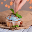 Female hand decorating tasty cupcake with butter cream, on color wooden table, on lights background — Stock Photo #40591859