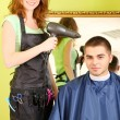 Beautiful girl hairdresser dries hair guy in beauty salon — Stock Photo