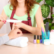 Stock Photo: Girl manicurist doing manicure for min beauty salon