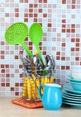 Pratos e talheres na cozinha, na mesa em mosaico azulejos fundo — Fotografia Stock