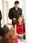 Young man hairdresser cut girl in beauty salon — Stock Photo