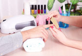Girl manicurist doing manicure for man in beauty salon — Stock Photo