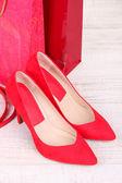 Hermosos zapatos femeninos rojos, correa y una tienda de bolsos — Foto de Stock