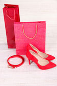 Beautiful red female shoes, belt and shop bags — Stock Photo