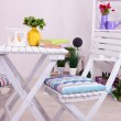 Garden chairs and table with flowers on shelves on white background — Stock Photo #40640281
