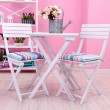 Garden chairs and table with flowers on shelves on pink background — Stock Photo