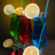 Glasses of cocktails on table on dark yellow background — Stock Photo