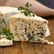 Tasty blue cheese with thyme, on wooden table — Stock Photo