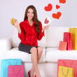 Beautiful young woman sitting on sofa with shopping bags and gift box on gray background — Foto de Stock